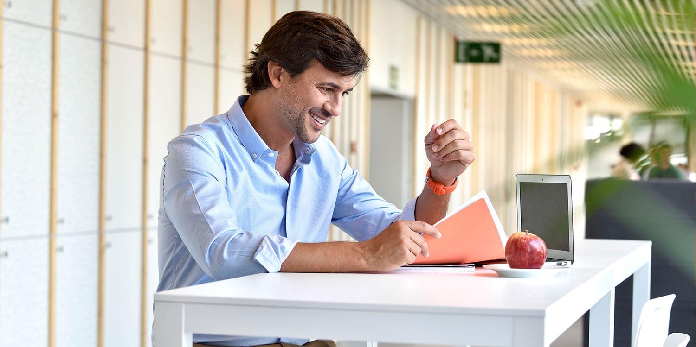 hombre mirando notas con portátil y manzana